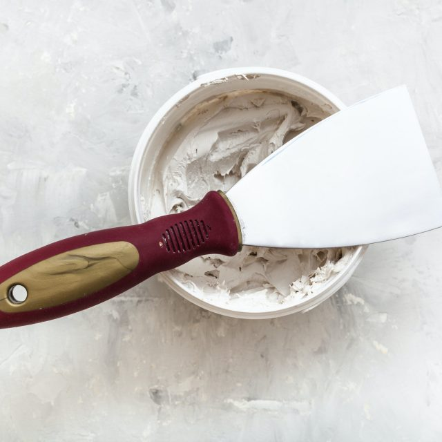 metal spatula on container with putty