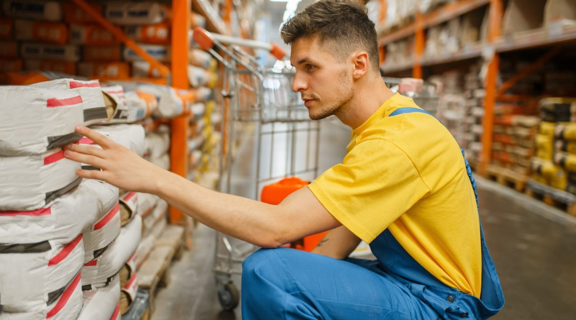 Male constructor choosing cement in hardware store